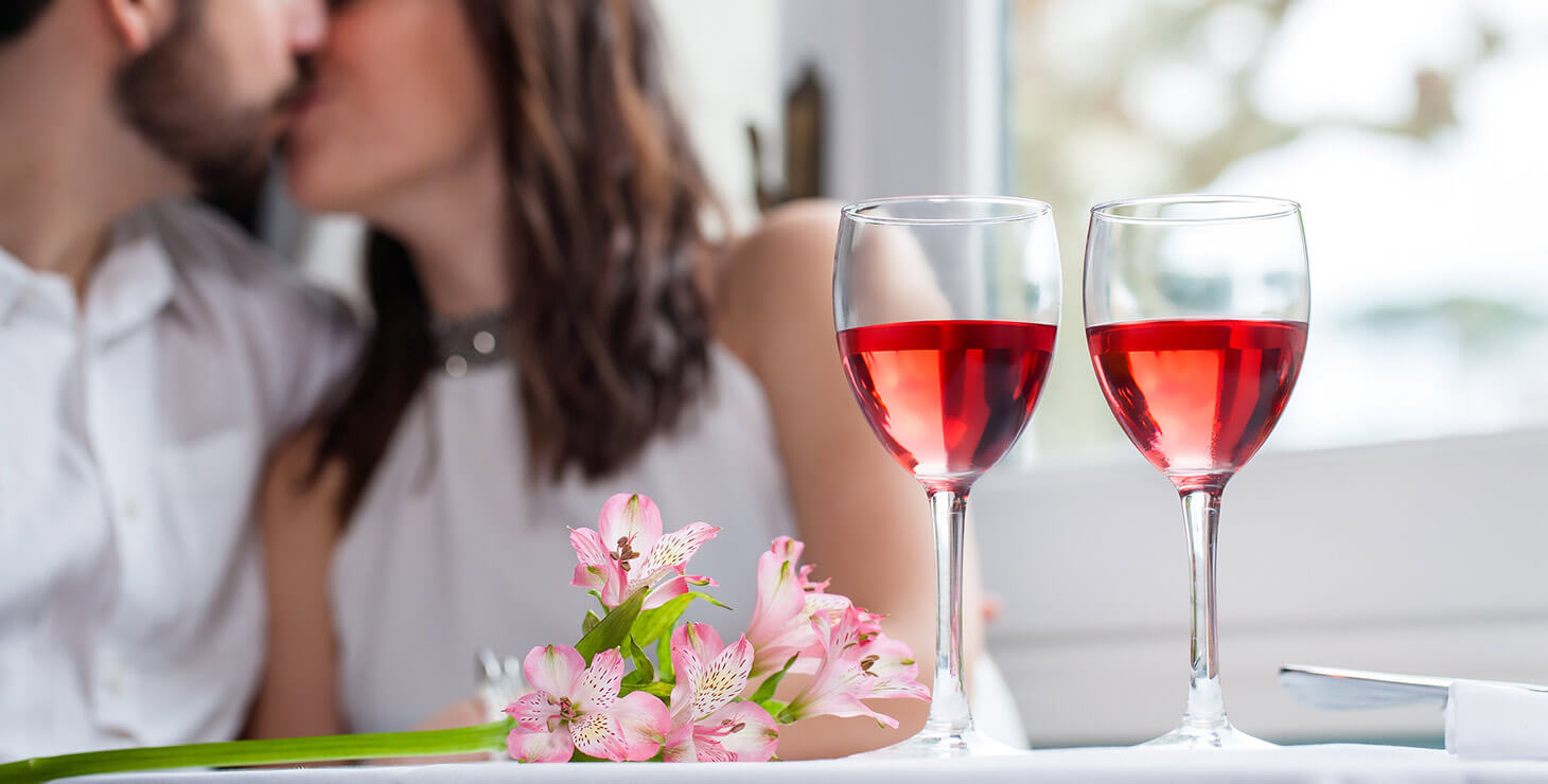 Finger Lakes Getaways - Wine and flowers with couple kissing in the background