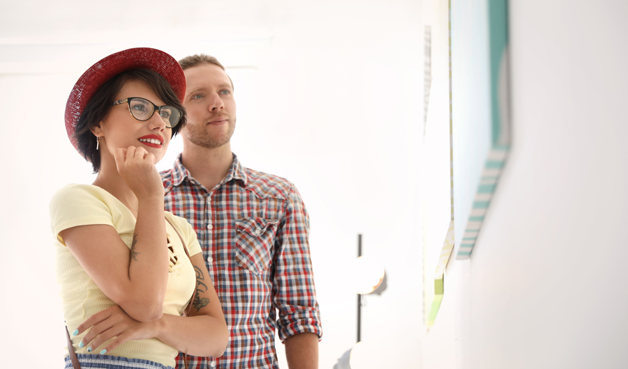 Woman in a red hat and glasses and man in a plaid shirt looking at art in a museum