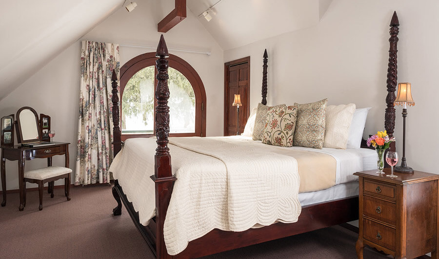 Romantic hotel room with hand-carved poster bed with an arched window behind