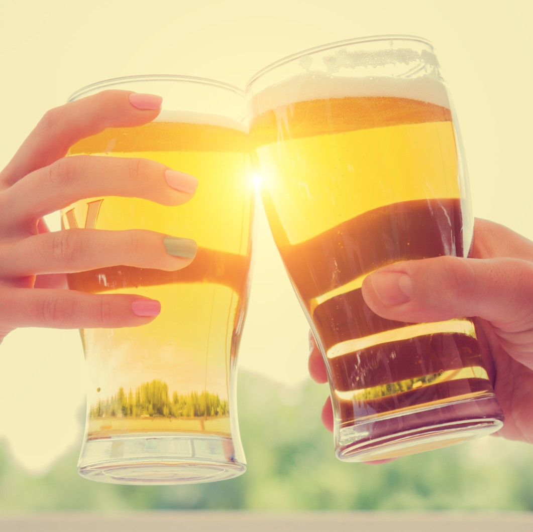 Close-up of two beers cheers in the sunshine